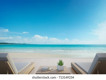 Sea view terrace and beds in modern luxury beach house with blue sky background, Lounge chairs on wooden deck at vacation home or hotel - 3d illustration of tourist resort