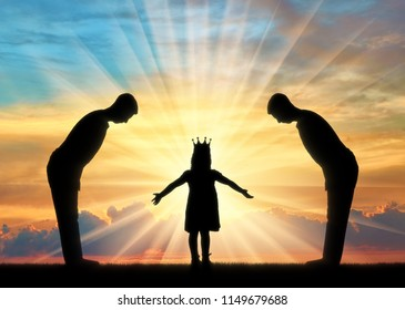Selfish little girl with a crown on her head and two servants worship her. Concept of spoiled, selfish children