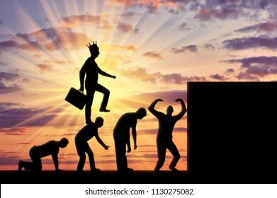 A selfish man with a crown on his head, walking on the heads of people as on the steps to the top. Conceptual scene of a narcissistic and selfish businessman