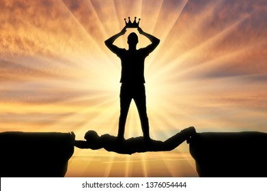 Selfish man puts a crown on his head, he stands on a man in the form of a bridge over a precipice. Concept of selfishness