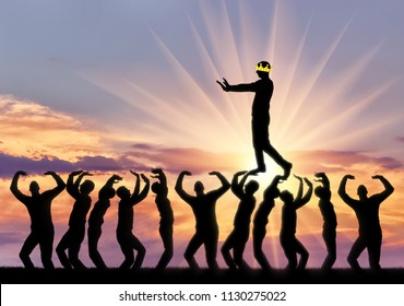 A selfish man walks the heads of people, he is blind, his crown closes his eyes to see. Conceptual scene of a narcissistic and selfish businessman