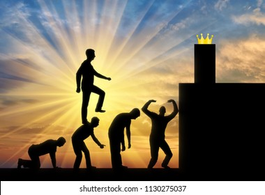 A selfish man walks the heads of people as on the steps to the highest post behind the crown. Conceptual scene is a narcissistic and selfish person