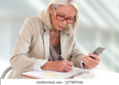 Senior woman executive with schedule and cell phone