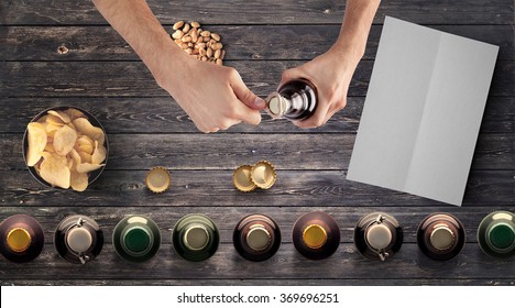 Set of beer bottles, snacks, clear menu paper and man opening bottle on wooden table, top view