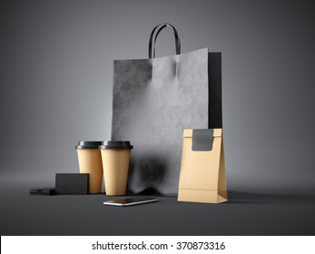 Set of black shopping bag, coffee cups, paper package, blank business cards and generic design smartphone. Dark background. 3d render