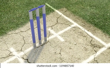 A set of blue cricket wickets on a cracked grass pitch background - 3D render