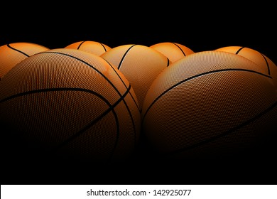 set of orange basketballs located on the court, with dim light on dark background
