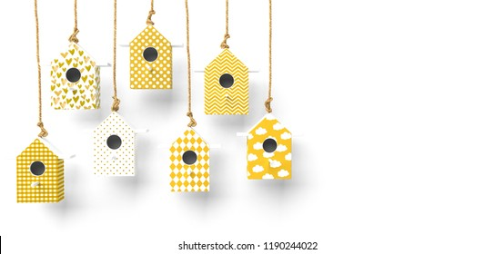 A set of painted birdhouses are suspended on a rope. Birdhouses with yellow and white patterns isolated on a white background with space for text. 3D rendering