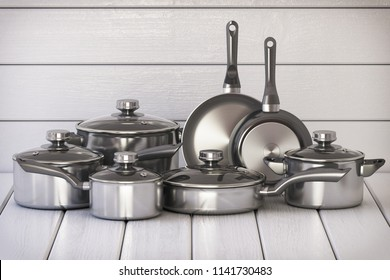 Set of stainless pots and pan with glass lids on the white wooden background. 3d illustration