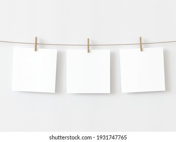 Set of three note paper cards hanging with wooden clip or clothespin on rope string peg isolated on white backgroun. 3D illustration