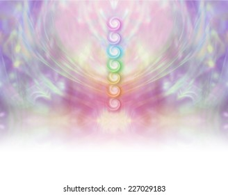 Seven Chakra Vortex Website Banner  -  Symmetrical pastel colored wispy misty background with vertical row of seven chakras place in center