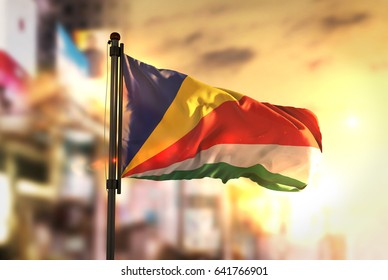 Seychelles Flag Against City Blurred Background At Sunrise Backlight 3D Rendering