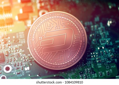 shiny copper DASH cryptocurrency coin on blurry motherboard background
