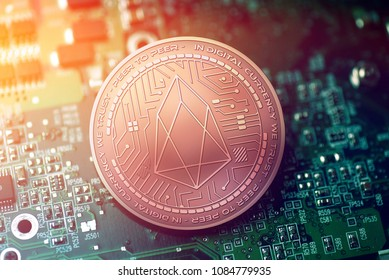 shiny copper EOS cryptocurrency coin on blurry motherboard background