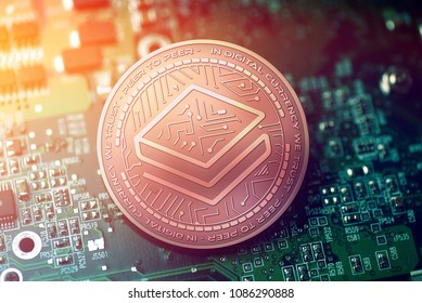 shiny copper STRATIS cryptocurrency coin on blurry motherboard background