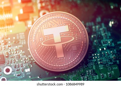 shiny copper TETHER cryptocurrency coin on blurry motherboard background