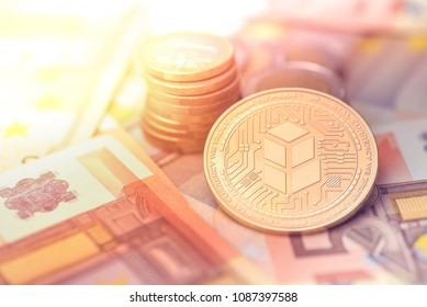 shiny golden BANCOR cryptocurrency coin on blurry background with euro money