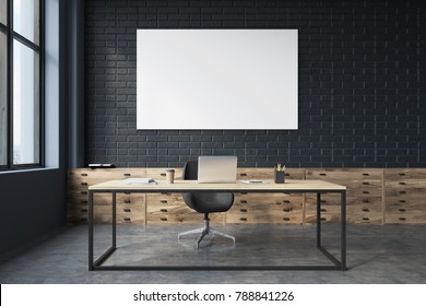 Side veiw of a black brick CEO office interior with a concrete floor, a large table with a computer on it and a poster. Front view. 3d rendering mock up