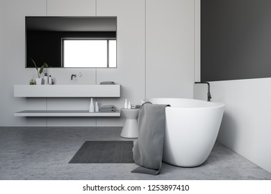Side view of bathroom interior with gray and white walls, concrete floor, white bathtub and white sink with horizontal mirror above it. 3d rendering