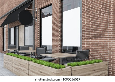 Side view of a brick restaurant exterior with square tables and gray chairs standing outside. A flowerbed. Posters 3d rendering mock up