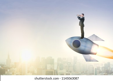 Side view of businessman flying on rocket ship and using binoculars to looking into the distance. Blurry city background with copy space. Start up, entrepreneurship and research concept