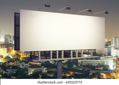Side view of empty poster on illuminated night city background. Advertisement concept. 3D Rendering