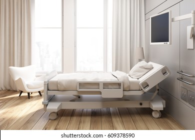 Side view of a gray walled hospital ward with a bed, a tv set, a white armchair and curtains on large windows. 3d rendering, Mock up