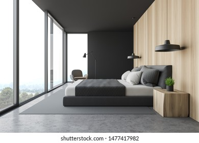Side view of master bedroom with gray and wooden walls, concrete floor, double bed, gray armchair and panoramic windows. 3d rendering