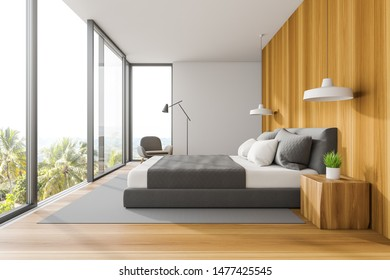 Side view of master bedroom with white and wooden walls, wooden floor, double bed, gray armchair and panoramic windows. 3d rendering