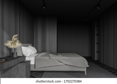 Side view of minimalistic master bedroom with grey and dark wooden walls, comfortable king size bed, table in home office area and shelves in background. 3d rendering