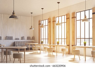 Side view of a modern cafe interior with concrete walls and floor, wooden shutters at tall windows and round tables with chairs. 3d rendering mock up toned image