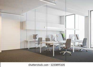 Side view of office workplace interior white white and glass walls, loft windows, carpet on the floor and rows of white computer tables with desktops and gray chairs. 3d rendering