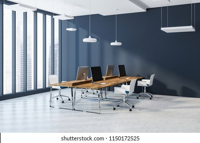 Side view of an open space office interior with dark blue walls, a concrete floor, rows of wooden computer desks and white chairs. Loft window with a cityscape. 3d rendering mock up