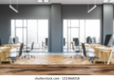 Side view of open space office with gray walls, wooden floor, large windows and rows of wooden computer tables with black chairs. Table in foreground. 3d rendering blurred