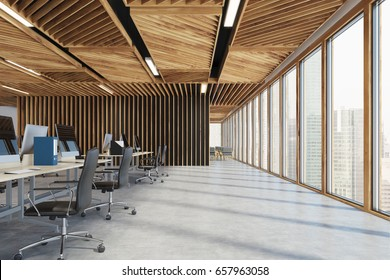 Side view of an open space office interior with wooden walls, concrete floor and two rows of computer tables along a wall and a panoramic window. 3d rendering mock up