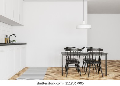 Side view of a Scandinavian style kitchen with white walls, a wooden floor, white countertops and cabinets and a table with black chairs. 3d rendering mock up