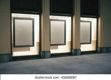 Side view of shop exterior with blank frames in glass showcase at night. Mock up, 3D Rendering