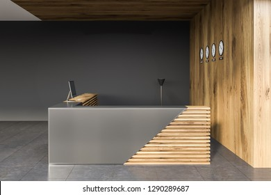 Side view of stylish gray and wooden reception desk with computer standing in modern office with gray and wooden walls and clocks. 3d rendering