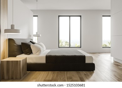 Side view of stylish master bedroom or hotel suite with white and wooden walls, wooden floor, king size bed and windows with tropical view. 3d rendering