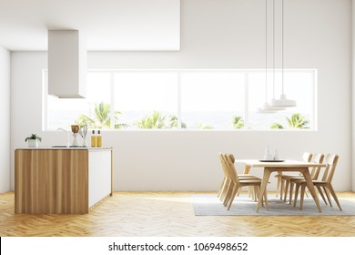 Side view of a white kitchen and dining room interior with a wooden floor, wooden countertops, a table and chairs and a large window. 3d rendering mock up