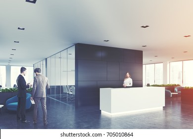 Side view of a white reception desk standing in an open space office environment with a black wall, rows of computer tables and loft windows. People 3d rendering mock up toned image