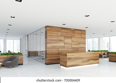 Side view of a wooden reception desk standing in an open space office environment with rows of computer tables and loft windows. 3d rendering mock up