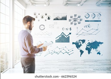 Side view of young businessman looking at document in bright concrete interior with city view and business charts on wall. Finance concept. 3D Rendering