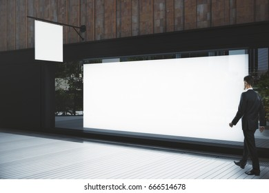 Side view of young businessman walking past empty vitrine with poster and stopper. Boutique ad concept. Mock up, 3D Rendering