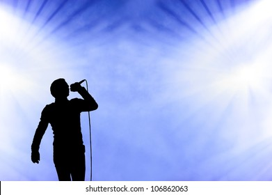 Silhoetted illistration of a male singer performing against a blue cloudy smoke filled sky at an open-air concert
