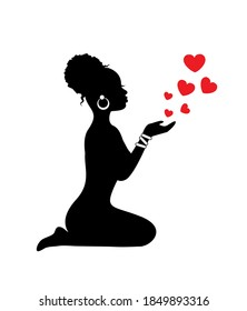 Silhouette African woman sits on her knees and sends red hearts