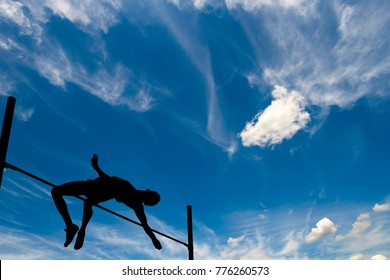 Silhouette of athlete jumping pole vault under the blue sky with clouds