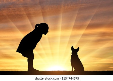 Silhouette of a baby girl and her dog looking at the sunset. The concept of children and their pets