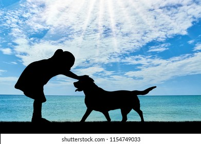 Silhouette of a baby girl stroking a dog against the sea. The concept of friendship with pets