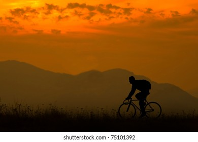 silhouette of a biker in a sunset mountain landscape